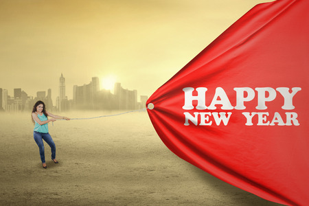 text year: Attractive indian woman pulling a big poster with an happy new year text