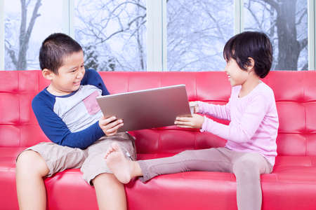sibling rivalry: Image of two children sitting on the sofa and fighting to take over laptop computer