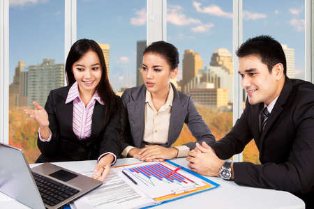 young entrepreneurs: Image of three young entrepreneurs discussing in the office using laptop computer with autumn background on the window Stock Photo