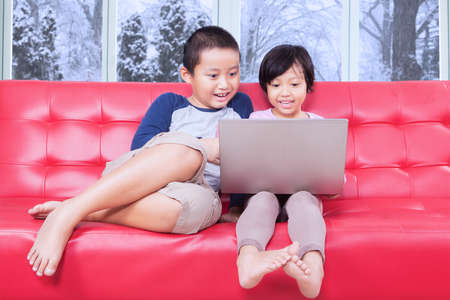 female child: Portrait of little girl and her brother using laptop computer on the sofa at home