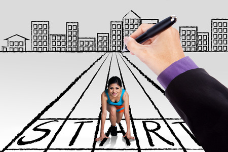 kneeling woman: Hand drawing a start line with a city and young woman kneeling on the start line ready to run Stock Photo