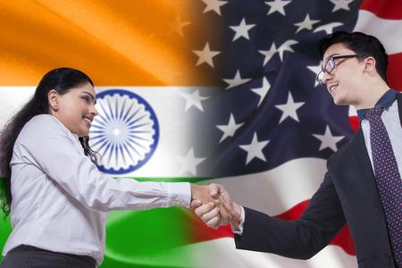 personas saludandose: India empresaria darse la mano con el empresario americano delante de las banderas de la India y de América Foto de archivo