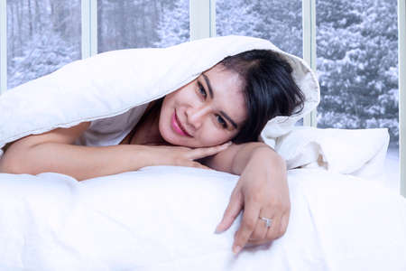 duvet: Portrait of beautiful female model smiling at the camera while lying on the bed under blanket with winter background on the window