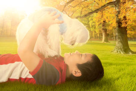 doggie: Portrait of cheerful little boy lying on the grass while playing with his dog at the autumn park Stock Photo