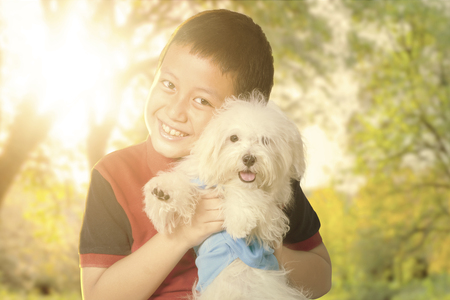 boy: Portrait of a cute little boy smiling at the camera while hugging his puppy at the autumn park