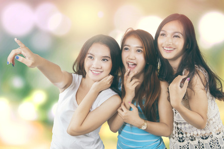 impressed: Group of three impressed teenage girls with casual clothes and looking at copy space, shot with light glitter background
