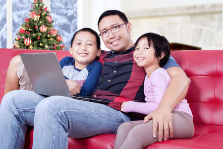christmas movies: Two happy children and their father smiling at the camera while sitting on the sofa with laptop computer Stock Photo