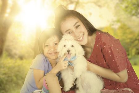 ragazza innamorata: Pretty bambina e sua madre seduto al parco mentre si tiene il loro cucciolo e sorridendo alla telecamera