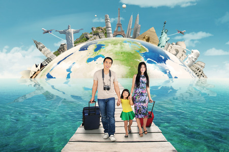 viaje familia: Dos padres jóvenes con su hija que llevan el bolso en el puente para viajar al monumento mundo