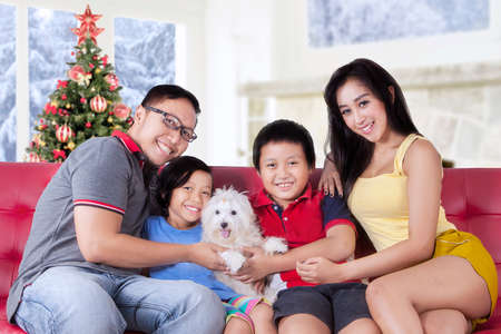 hispanic kids: Portrait of happy family smiling at the camera while sitting on the sofa and holding a dog, shot with a christmas tree background
