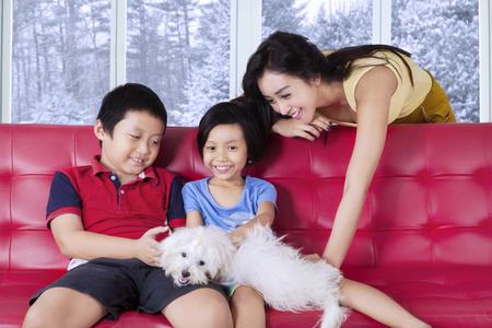 niñas jugando: Bastante joven madre jugando un perro con sus hijos en el sofá de casa, tiro con fondo de invierno en la ventana Foto de archivo