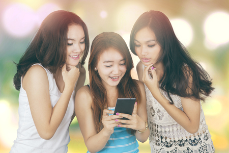 happy asian people: Group of three beautiful teenage girls reading message together on the mobile phone, shot with bokeh background