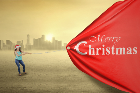 christmas woman: Young asian woman wearing christmas hat and pull a big poster with a merry christmas text