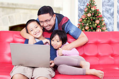 christmas movies: Portrait of cheerful young father and his children watching movie with laptop on sofa, shot with a christmas tree background Stock Photo