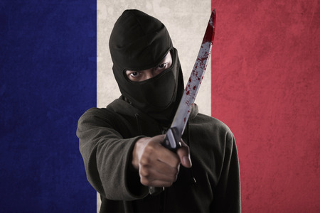 Terorrism concept: terroris threatening with a knife in front of France national flag