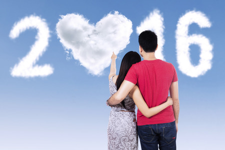 japanese symbol: Back view of young couple with casual clothes, looking at clouds shaped numbers 2016 Stock Photo