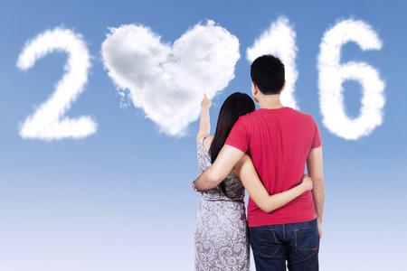 couple  amoureux: Num�ros Vue arri�re du jeune couple avec des v�tements d�contract�s, en regardant les nuages ??en forme de 2016 Banque d'images