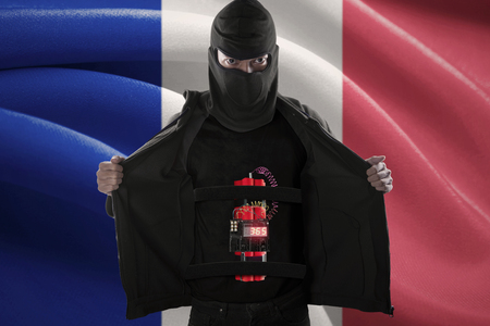 detonating: Terrorism concept: Jihadist showing a time bomb sticking on his body in front of France flag Stock Photo