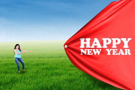 text year: Young asian woman pulling a red poster with a Happy New Year text Stock Photo