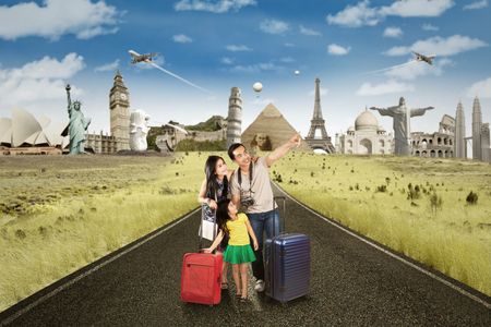 Happy family standing on the road while carrying luggage and looking at famous landmarks