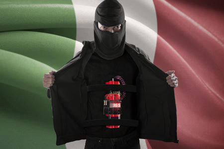 radical: Terrorism concept: Male radical muslim sticking a time bomb on his body in front of Italy flag