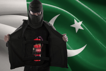 detonating: Terrorism concept: Terrorist showing a time bomb sticking on his body in front of Pakistan flag Stock Photo