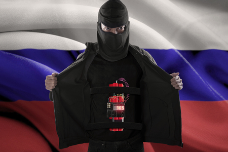 time bomb: Terrorism concept: Male radical muslim sticking a time bomb on his body for suicide attack in front of Russian flag Stock Photo