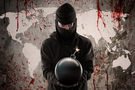 Terrorism concept: Jihadist wearing mask and holding a bomb in front of bloody world map Фото со стока - 48553845