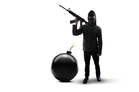 to rebel: Terrorism concept: Male rebel with mask, standing in the studio with bomb and holding machine gun