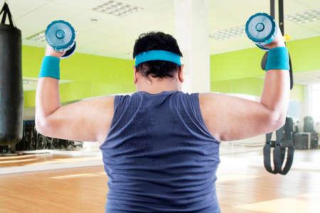 levantando pesas: Hombre gordo ejercicio con dos pesas en el gimnasio Foto de archivo