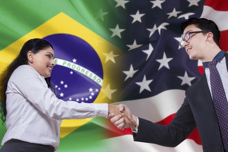 brazil symbol: Photo of young brazilian businesswoman shaking hands with american person in front of Brazilian and American flags Stock Photo