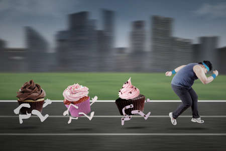 fat food: Overweight person wearing sportswear and run on track for escaping from cupcakes Stock Photo