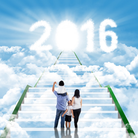 stairway: Rear view of happy family climbing the staircase on the cloudscape toward numbers 2016 with an entrance to the heaven