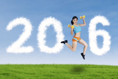 indonesian woman: Pretty young woman wearing sportswear, holding two dumbbells and jumping at field with numbers 2016