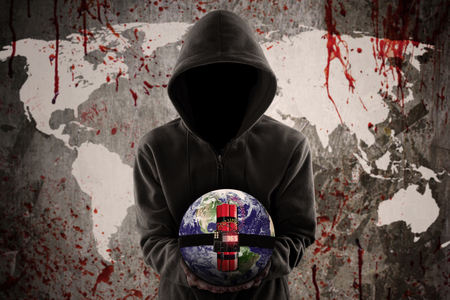 Terrorism concept: Anonymous terrorist holding a time bomb with bloody world map Stock Photo