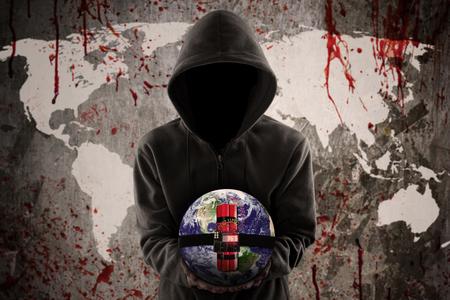 Terrorisme notion: terroriste Anonyme tenant une bombe à retardement sur la carte sanglante du monde