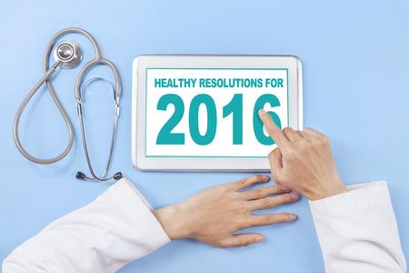 Afbeelding van de arts de hand met behulp van tablet om te schrijven gezonde resolutie voor 2016 op het scherm Stockfoto