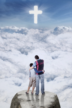 son of god: Image of young father standing on the cliff with his son and looking at a cross symbol on the sky