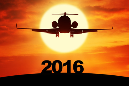 new year: Silhouette of aircraft flying on the sky above numbers 2016, shot at sunset time Stock Photo