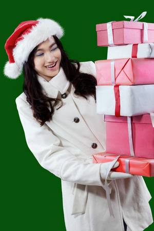 female beauty: Portrait of cheerful young girl wearing winter coat and holds many christmas gift with green background