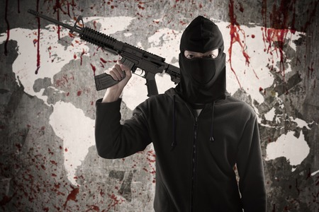 Terrorism concept: Male radical muslim wearing mask and holding a rifle in front of bloody map