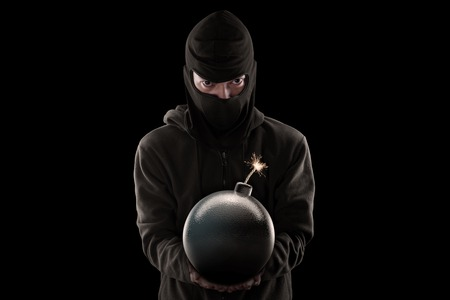 tnt: Terrorism concept: Male jihadist holding a bomb and wearing mask with dark background