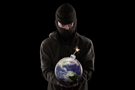Terrorism concept: Male terrorist wearing mask and holding a bomb with globe
