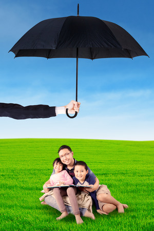 umbrella: Portrait of happy father and his children sitting on the meadow while reading a book under umbrella Stock Photo
