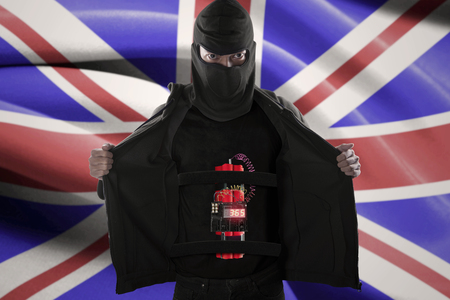 radical: Terrorism concept: Male radical muslim showing a time bomb on his body for suicide attack in front of United Kingdom flag