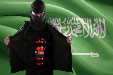 terrorism: Terrorism concept: Male terrorist with mask and showing a time bomb on his body in front of Saudi Arabia flag