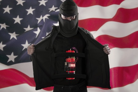 american flag: Terrorism concept: Bomber suicide showing a time bomb on his body in front of American flag