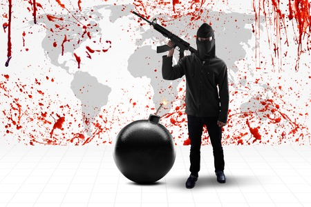 iraq war: Terrorism concept: Male terrorist standing in front of a background of bloody world map while holding weapon with bomb