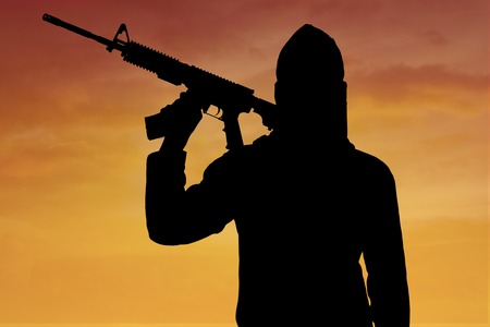 radical: Terrorism concept: Silhouette of male radical muslim holding a machine gun