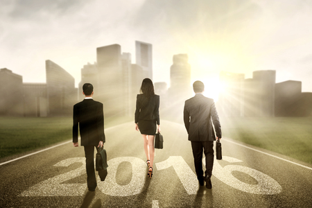 road to success: Group of three businesspeople walking together on the road with numbers 2016 toward the city Stock Photo